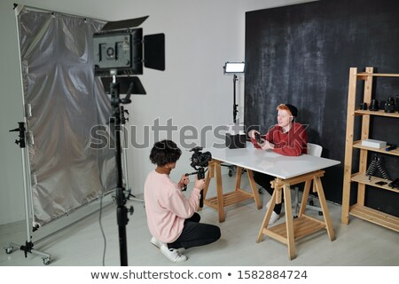 Young vlogger telling about new photo equipment in front of operator Stock photo © pressmaster