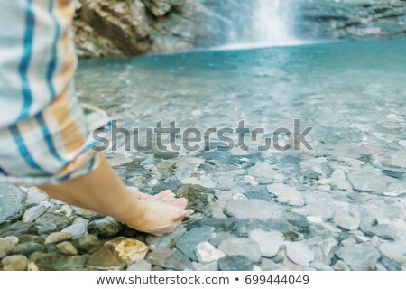 Stock fotó: Young Woman Drinking Water Near A Waterfall