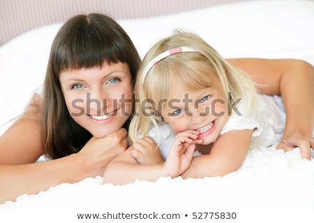 mother and daughter posing happily in bed stock photo © dacasdo