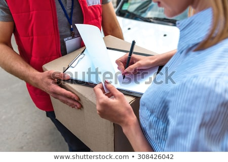 Woman signing for a courier delivered parcel Stock photo © photography33