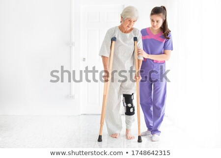 doctor helping an elderly woman use a crutch stock photo © photography33