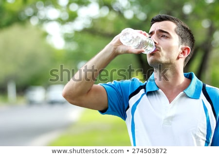 boy is sweating and thursty  and drinks mineral water Stock photo © meinzahn