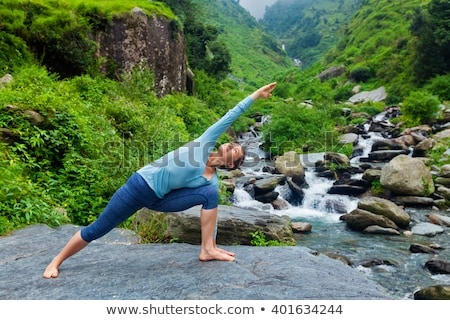 Woman practices yoga in nature, the waterfall. parsvakonasana pose stock photo © Geribody
