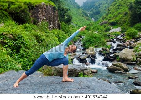 Woman practices yoga in nature, the waterfall. parsvakonasana pose Stock photo © Geribody