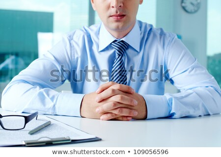 Close-up of businessman keeping fingers crossed in front of himself Stock photo © deandrobot