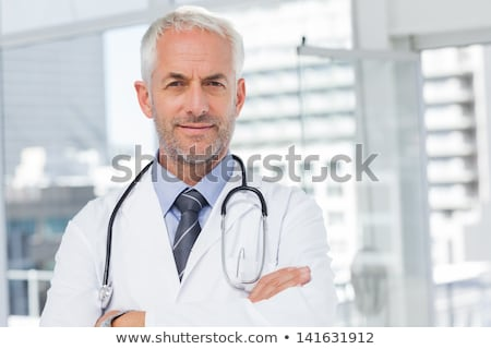 smiling male doctor standing with arms folded stock photo © deandrobot