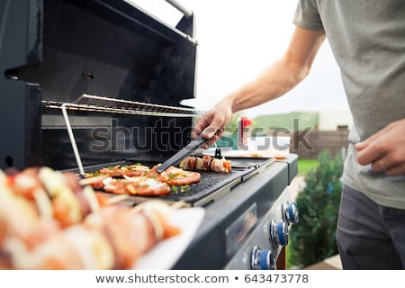 Man cooking meat on gas barbecue grill. Stock photo © RAStudio