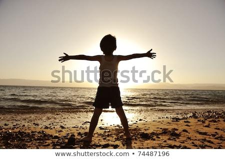 Silhouette enfant sable plage eau été Photo stock © mmarcol