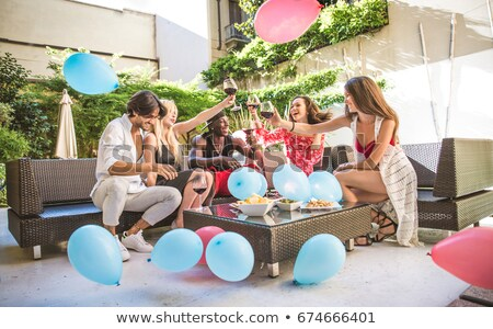 Stock photo: Happy young man with friends sitting at nightclub