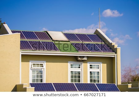 Row of Photovoltaic Solar Panels on Roof Against Blue Sky       stock photo © Qingwa