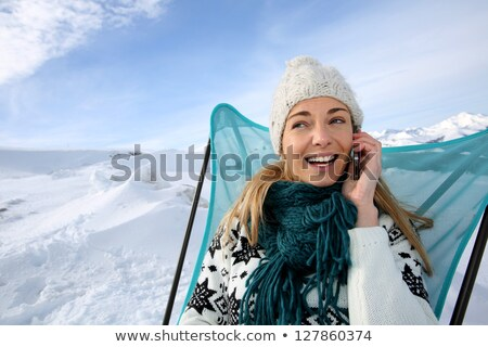 woman sitting in the snow using phone stock photo © is2