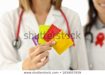 woman doctor with stethoscope hold condom stock photo © traimak
