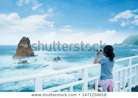 Girl using instant camera on beach Stock photo © IS2