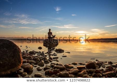 pretty blonde meditating on a beach stock photo © konradbak