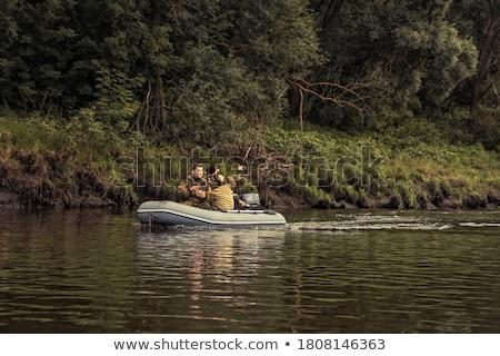 Pêche bateau à moteur banque permanent séance poissons Photo stock © robuart