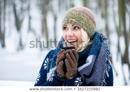 woman freezing on a cold winter day warming herself up with hot drink stock photo © kzenon