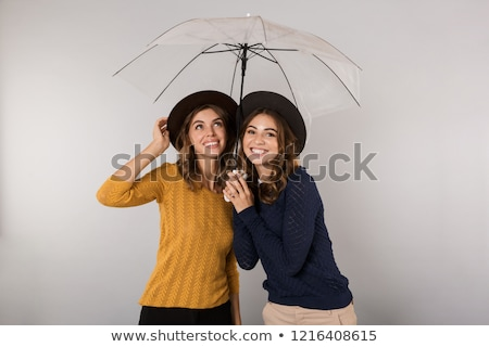 Image of two pleased women wearing hats standing under umbrella, Stock photo © deandrobot