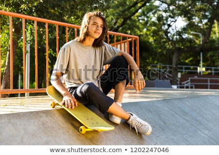 Photo of pleased skater boy 16-18 in casual wear sitting on ramp Stock photo © deandrobot