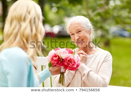 daughter giving flowers to senior mother at park stock photo © dolgachov