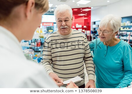 Pharmacist getting prescription slip from senior couple Foto stock © Kzenon