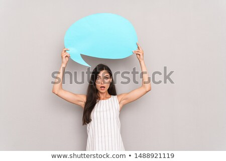Woman posing isolated over grey wall background holding thought bubble. Stock photo © deandrobot