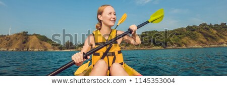 Smiling young woman kayaking on sea. Happy young woman canoeing in sea on a summer day BANNER, long  Stock photo © galitskaya