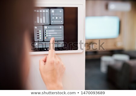 Stockfoto: Hand Of Young Woman Touching One Of Digital Buttons On Smart Remote Control
