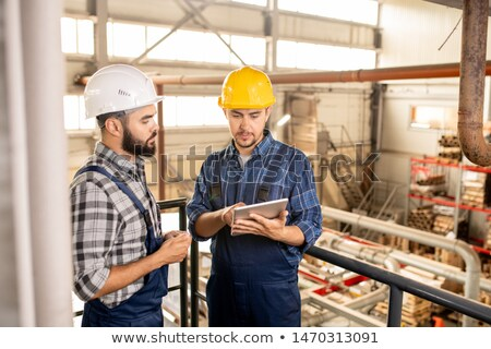 one of young contemporary engineers showing his colleague online information stock photo © pressmaster