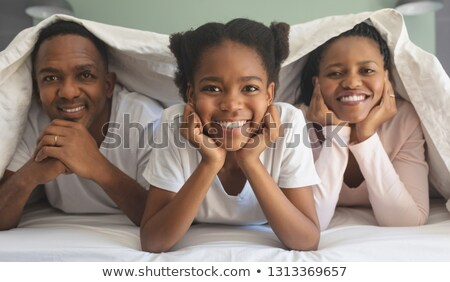 Front view of happy African American family under blanket and looking at camera on bed in bedroom at Stock photo © wavebreak_media