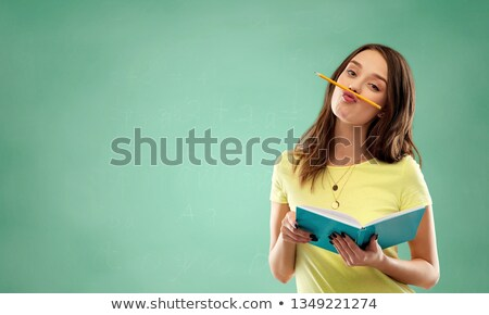 student girl with book and pencil over green Stock photo © dolgachov