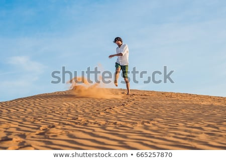 A man is kicking sand in a red desert. Splash of anger concept Stock photo © galitskaya