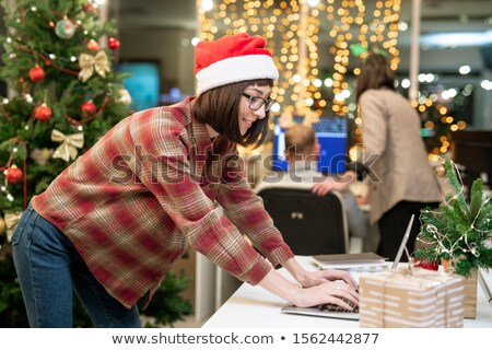 Young businesswoman in Santa cap looking at laptop display while organizing work Stock photo © pressmaster