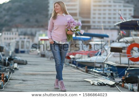 A female tourist walks along a wooden pier where fishing boats are tied up Stock photo © ElenaBatkova