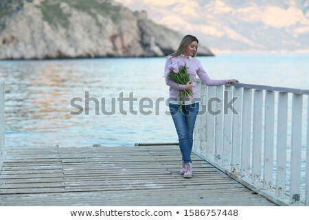 A woman in full figure standing on a wooden pier on the background of mountains Stock photo © ElenaBatkova