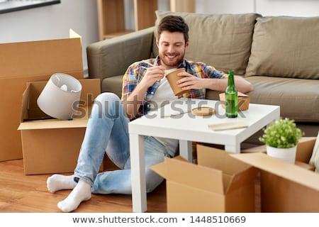 smiling man eating takeaway food at new home Stock photo © dolgachov