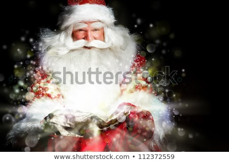 Santa sitting at the Christmas room and looking into the sack stock photo © HASLOO