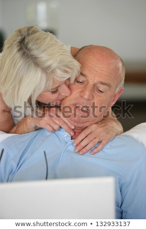 mature lady kissing her husband browsing with laptop Stock photo © photography33