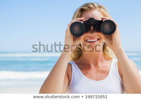 Attractive woman with binoculars at ocean stock photo © roboriginal