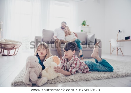 Happy family of four lying on the carpet Stock photo © get4net