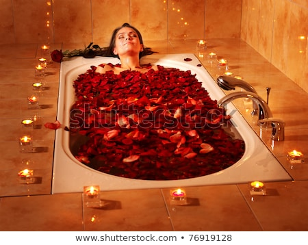 happy woman in a bath with rose-petals Stock photo © ssuaphoto