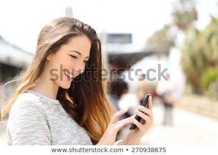 Gyönyörű lány sms sms üzenetküldés alkalmazás okostelefon nő Stock fotó © HASLOO