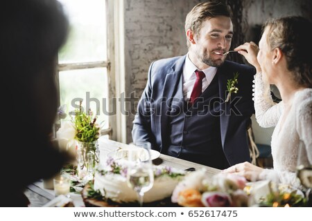 groom feeding bride with wedding cake at reception stock photo © monkey_business