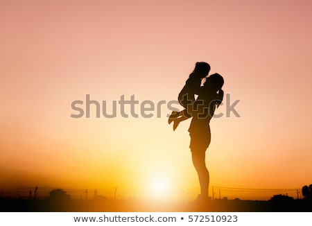 Happy family with little girl on beach in evening, parents lift  Stock photo © Paha_L