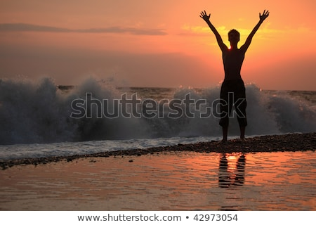 Silhouette guy lifted hands upwards on sunset wavy beach Stock photo © Paha_L