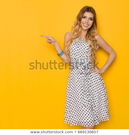 Smiling charming woman in dress looking at camera stock photo © deandrobot