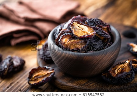 prune dried plums fruits on dark rustic wooden background stock photo © yelenayemchuk