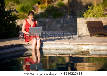 Woman dangling her feet in pool Stock photo © IS2