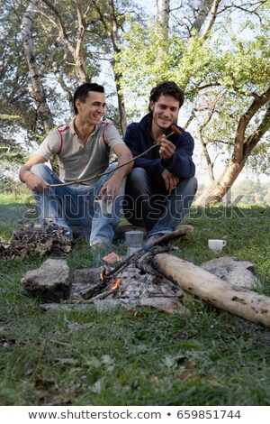 Two men cooking hot dogs over a fire pit Stock photo © IS2