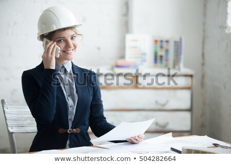 Woman in hard hat holding drafts Stock photo © IS2