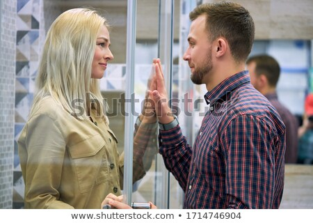 Couple looking through window, smiling Stock photo © IS2